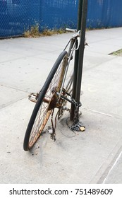 Abandoned broken and rusty bicycle chained to a metal pole on a pavement
