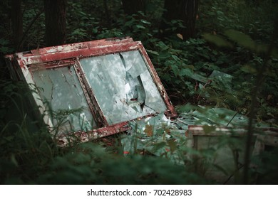 Abandoned broken windows in the forest. Pollution of the environment
