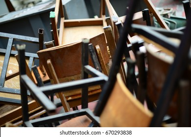 Abandoned broken wooden chair and desk in storage room. Missing school age. Old school and education concept.