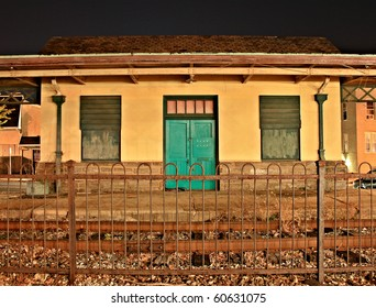 Abandoned building with a bright teal door at night