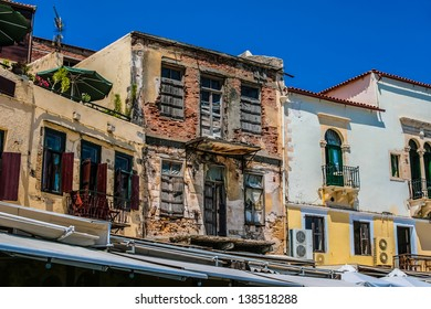 Abandoned building with broken wall at one of the streets in city of Chania on island of Crete, Greece, close to modern buildings of this city