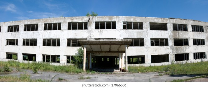 Abandoned building with broken windows. Panoramic front view