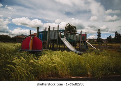 Abandoned Building and Playground with Grasses and Beautiful Cloudy Sky