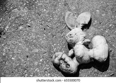 Abandoned bunny doll on the pavement. Black-white tone