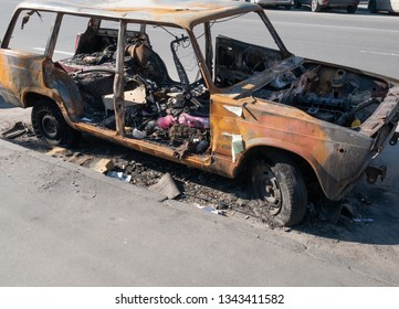 abandoned burned old car auto after riot on street transformed into trashcan. depict vehicle insurance service