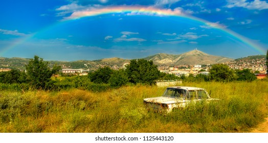 An abandoned car decomposing under a rainbow