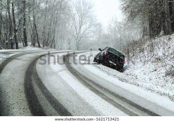 Abandontes Auto im Graben nach dem Verkehrsunfall. Symbolisiert die gefährlichen Bedingungen im Winter mit Eis, Schnee und Schnaps.
