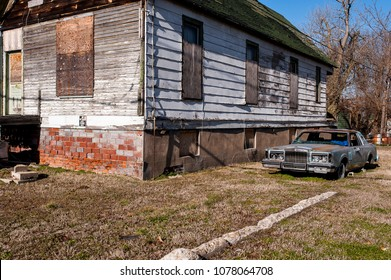 An abandoned car rests outside of an equally derelict house in the river town of Cairo, Illinois.