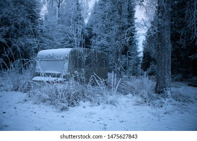 Abandoned caravan in winter forest in swedish woods