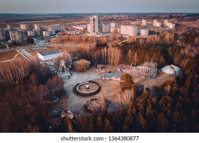 Abandoned carousel park and panorama of Elektrenai city. This abandoned park is in Elektrenai city in Lithuania, but feels like being in Chernobyl. Drone photo.
