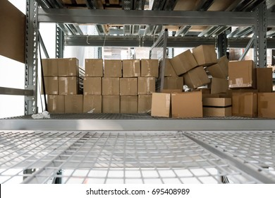 Abandoned carton boxes on steel racks with metal beam construction in storage