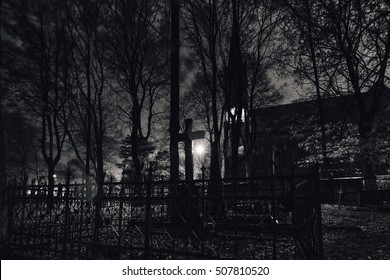 Abandoned cemetery at night. Windy and rainy night. Low light conditions for atmosphere of fear. Black metal and dark ambient music album cover. Eternal autumn. Fall. Loneliness and melancholy.