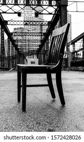 Abandoned chair in front of an abandoned factory in the wharf of Boston. The modern cit skyline in the background contradicting with the abandoned view