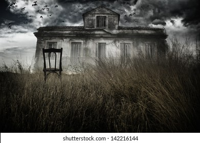 Abandoned chair out in a field facing a haunted house