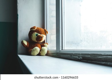 Abandoned children's toy teddy bear unhappy child sits on the sills alone in the entrance and looks out the window