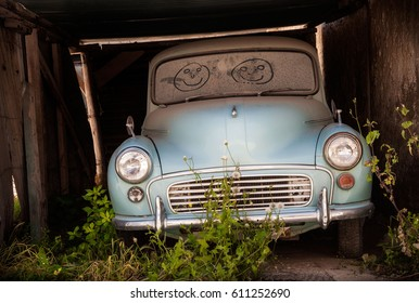 Abandoned classic car with smiling faces drawn in the dusty windscreen