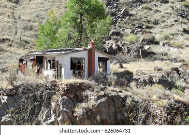 An abandoned and collapsing house at the bottom of a mountain hearkens back to an earlier time