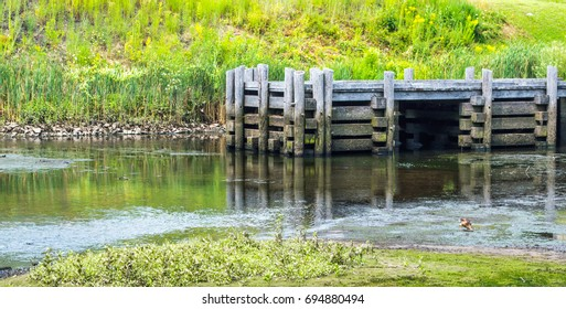 abandoned colonial wooden pier with log pilings on a shallow river