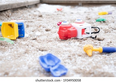 Abandoned colorful toys in sandbox at empty public playground. Kids toys scattered around in snowy frozen sandbox during winter lockdown.