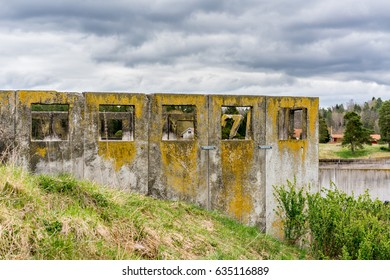 Abandoned concrete ruin on grass hill with square openings against cloudy sky.