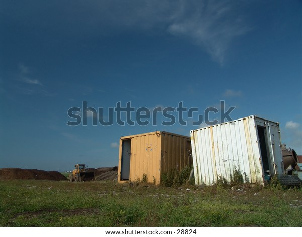 Abandoned containers with a wheel loader in the background