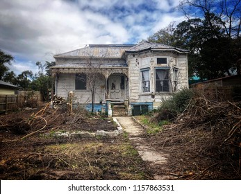 Abandoned decrepit old Victorian weatherboard house with iron lacework on verandah