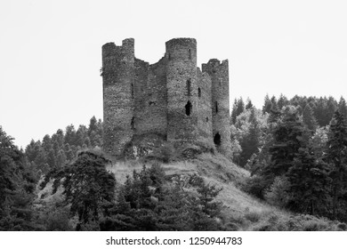 Abandoned and desolate castle in the south of France, with four towers on the top of a hill