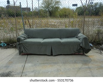 Abandoned and discarded couch outdoors with the garbage
