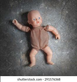 Abandoned doll laying on a concrete floor