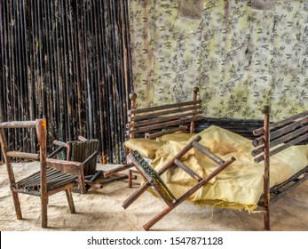 Abandoned dollhouse bedroom interior with bed and broken down furniture.