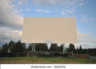 Abandoned drive-in screen with sky and grass