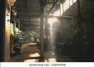 abandoned factory building, with barrels and equipment, vintage and atmospheric, a lot of pipes, cables, oil production, a ray of light