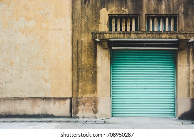 abandoned factory building, old yellow storage warehouse building with closed green metal roller shutter door in vintage effect, copy space, Taipei, Taiwan