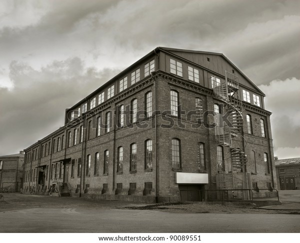 Abandoned factory building in sepia tone. Symbol for economic depressions.