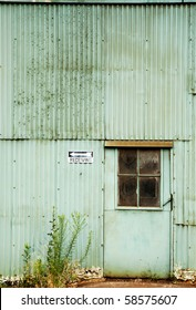 "Abandoned Factory with Green Corrugated Metal Walls, Weeds, Door and Receiving"" Sign"""