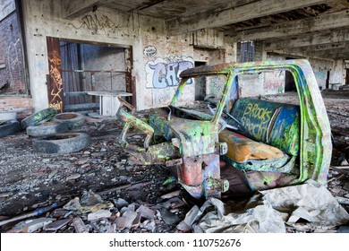 Abandoned factory with a truck chassis spray painted with graffiti.