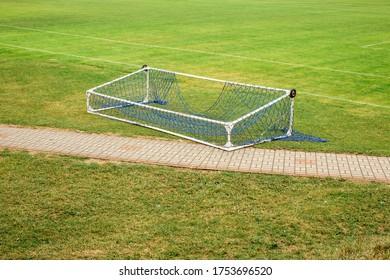Abandoned fallen soccer football gate lying on empty green field