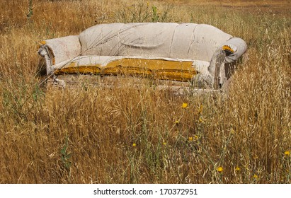 an abandoned falling apart couch in a fiels of long brown grass.