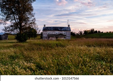 An abandoned farm house viewed on a beautiful pink and blue hued sunset on a partly cloudy evening in central Kentucky.