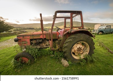 Abandoned farm machinery including a tractor and Landrover left to rust and deteriorate in a farmers field, Peak District, England, UK