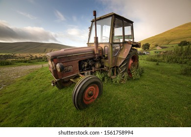 Abandoned farm machinery including a  tractor and Landrover in a farmers field, Peak District, England, UK