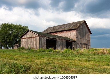 Abandoned farm with old red barns surrounded by dark clouds. Gives the feeling of trouble, a storm brewing for farmers. Concepts of family farm, trade wars, tariffs