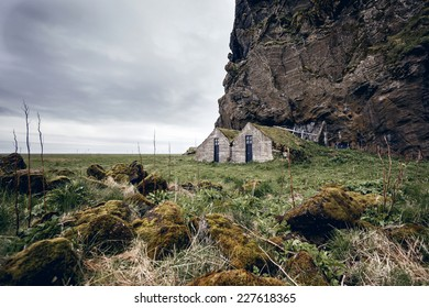 Abandoned farm under a lava rock face, Iceland