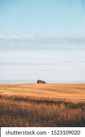 Abandoned farmhouse on the prairies at sunrise