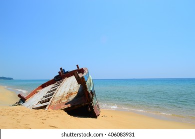 Abandoned fishing boat by the beach on a sunny day.