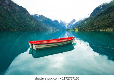 Abandoned fishing boat on Oldevatnet fjord and view to the rocks of Briksdalsbreen glacier. National touristic route of Norway. Morning lake glowing by sunlight.