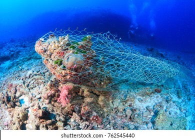 An abandoned fishing net (Ghost net) stuck on a tropical coral r