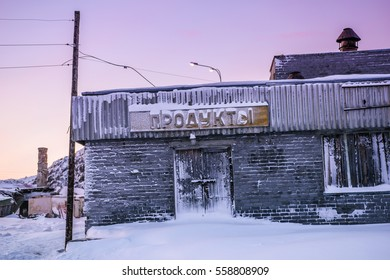 "Abandoned food store with the label in russian language. Teriberka settlement, Murmansk Region, Russia. Translation of the text from Russian is ""food"""