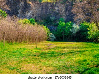 An abandoned football field with a rusting football goal slowly overgrown with greenery, under a rock