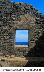 Abandoned fort in Aruba featuring an open window view of perfect blue waters